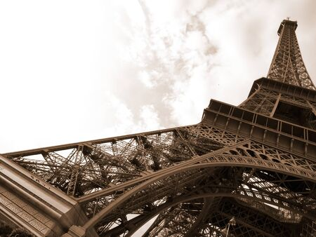 Eiffel tower against a sky background in sepia color.