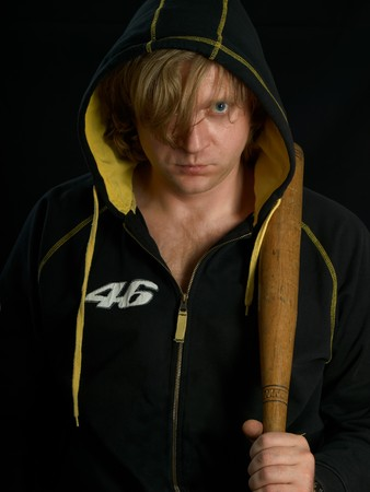 Man with baseball bat against a black background. photo