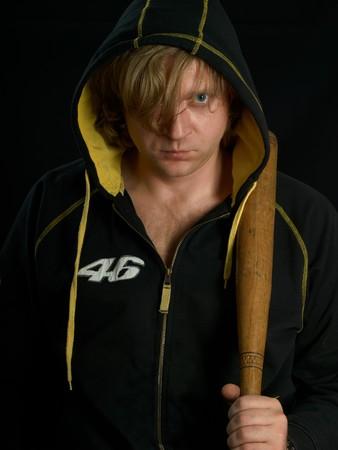 Man with baseball bat against a black background.