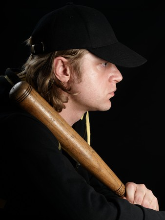 Mans profile portrait with baseball bat against a black background. photo