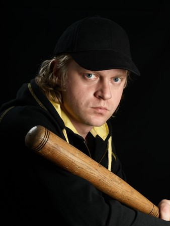 Mans fullface portrait with baseball bat against a black background. photo