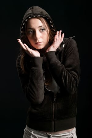 diverging: Young girl in hood is diverging with hand near face against a dark background