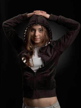 Young girl in hood is smiling against a dark background