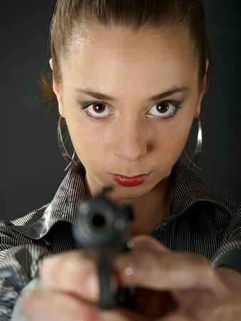 The beautiful girl with a gun against a dark background Stock Photo - 4970012