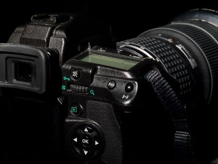 proffesional: Digital photo camera from back side in dark tone. Stock Photo