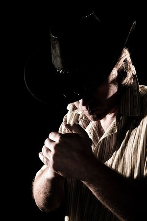 Man in cowboy hat with sloped head in sepia tone photo