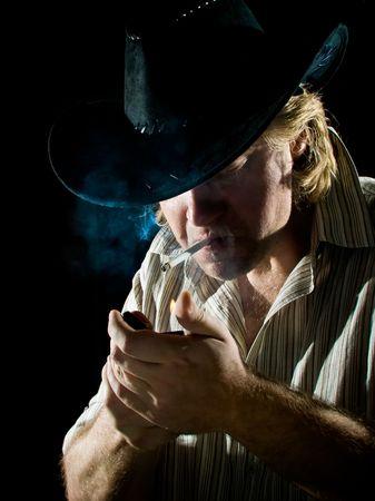 Man in cowboy hat lights a cigarette in dark photo