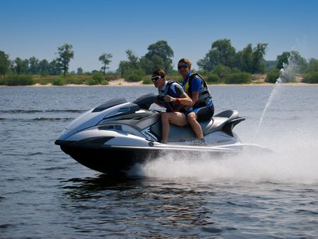 Couple men on jet ski skim along like an arrow from the bow