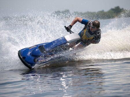 Man on jet ski turns left with much splashes photo