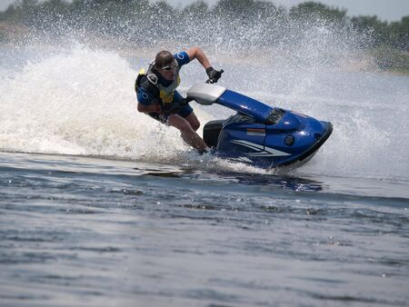Man on jet ski in the river turns with much splashes Stock Photo