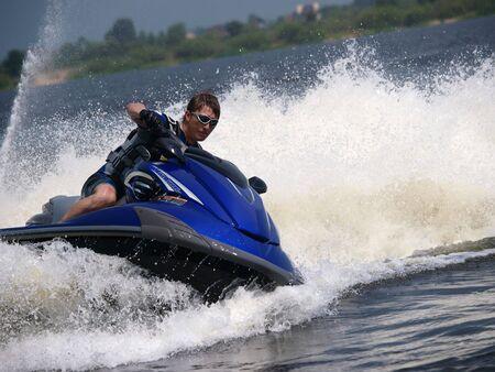 Man on WaveRunner turns left with much splashes Stock Photo