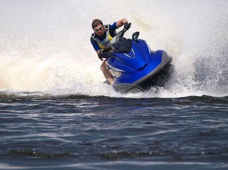Man on Wave Runner rides fast with much splashes