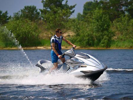 pleasure craft: Man on Wave Runner skims along against summer bank