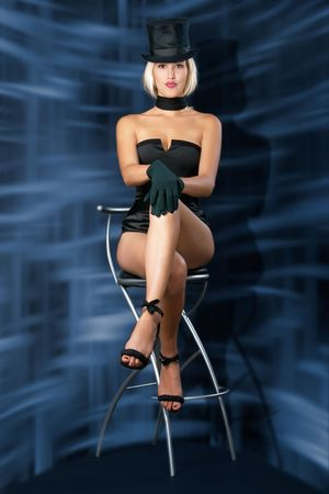 Cabaret showgirl is sitting on bar chair against an abstract background. Stock Photo