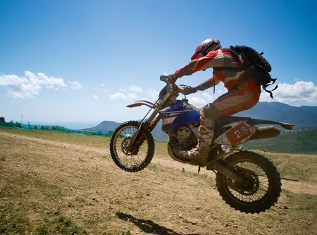 Off-road rider is jumping against a summer mountains
