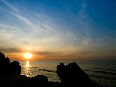 Sunset at the sea with silhouette of stones