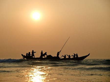 india fisherman: Fishers on boat in sunset on the sea Stock Photo