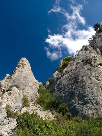 Rocks with trees against blue sky photo