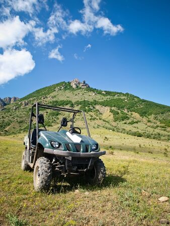 outdoorsman: Moto all-terrain vehicle nelle montagne contro il cielo blu