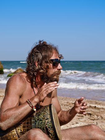Man drum on tam-tam on the beach  Stock Photo