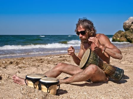 Man drum on tam-tam near the sea against a blue sky