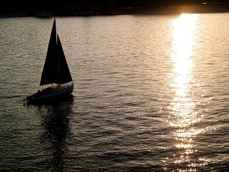 Yachts silhouette against a sun light on a river