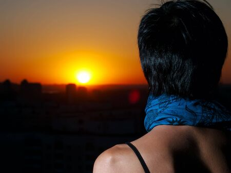 Girl from back looks on sunset from cities roof