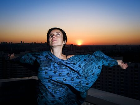 Woman on a roof against a sunset with outstretched arms
