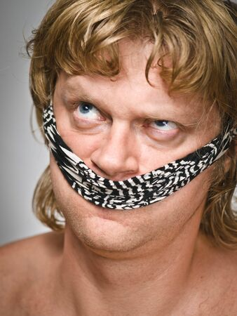 Man's portrait with bandaged one's mouth like a gag photo
