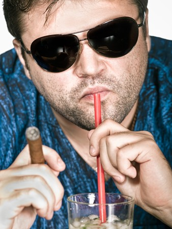 Brutal man in glasses keeps a cigar and drinks a cocktail