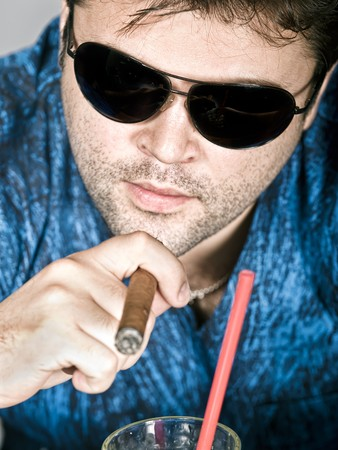 supercilious: Brutal man in glasses keeps a cigar near a cocktail Stock Photo