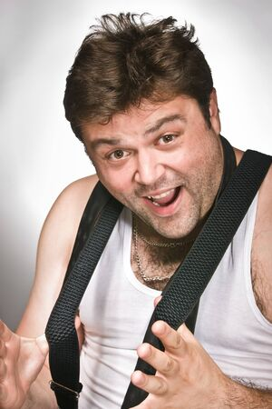 Fun man in white tank top stretchs his suspenders