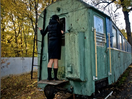 Woman strands on back side of old squalid rail coach Stock Photo - 7576032