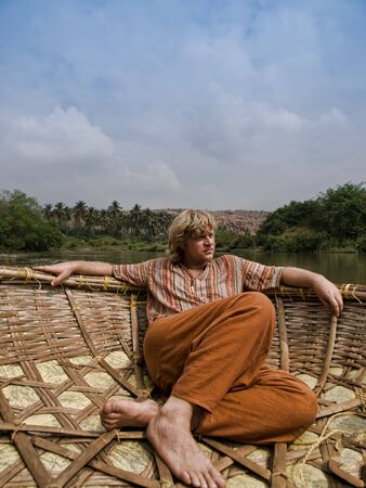 Caucasian man in Indian traditional clothes sailing in round boat-basket photo