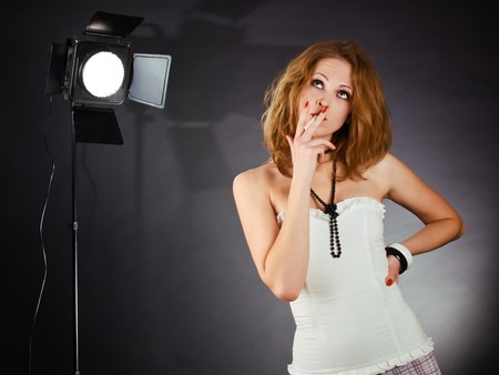 Young woman in dark studio like a backstage of photosession Stock Photo