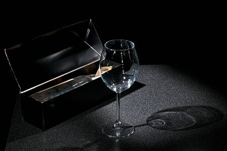 Glass and old wine in box in a dark tone photo