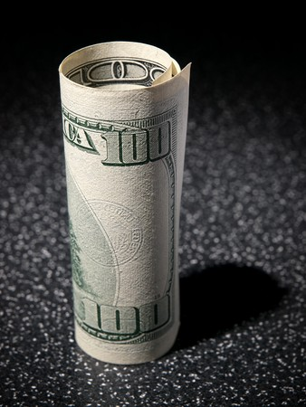 greenback: American 100 dollars greenback rolled up on the black Stock Photo