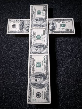 Cross figure is composed from one hundred dollars bank notes Stock Photo
