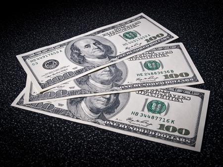 greenbacks: Three 100 dollars greenbacks lie on dark surface