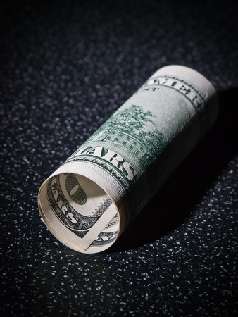 greenback: American 100 dollars greenback rolled lies on the black