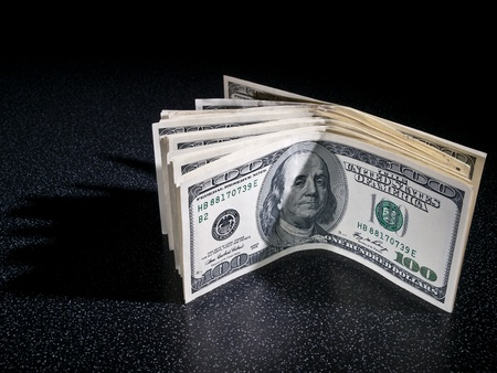 greenbacks: Pile of dollars greenbacks stans in dark background