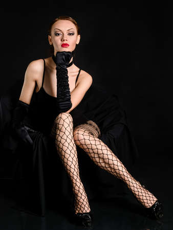 Sitting beauty girl with meshed stocking in dark studio photo