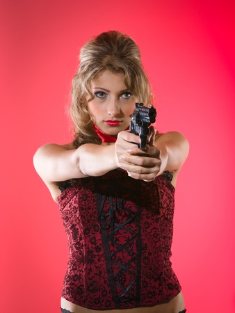 Beauty girl with revolver against a red background photo