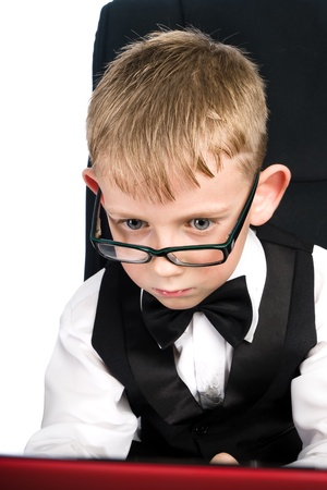 Child in white shirt and bow tie looks in laptop photo