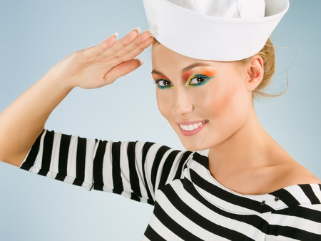 salutes: Smiling young woman in sailors cap salutes like a greeting Stock Photo