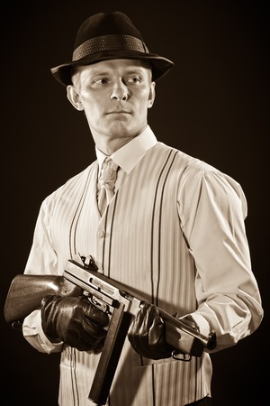 Retro style - Man keeps a Thompson submachine gun in sepia tone  photo