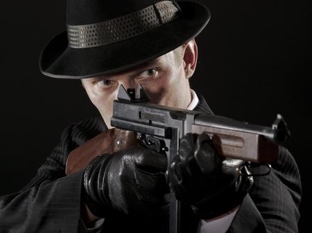 Man aims at Thompson submachine gun