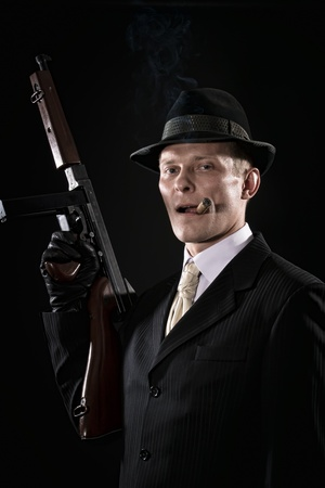 fedora: Man with a cigar like a chicago gangster with Thompson gun Stock Photo