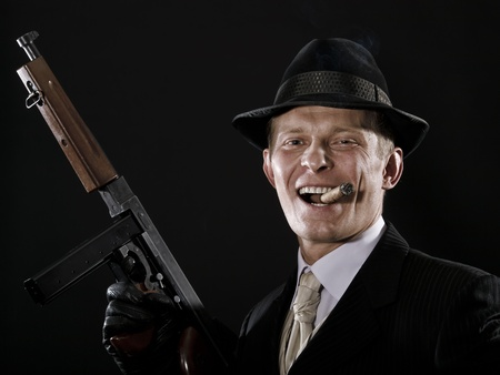 Laughing man like a chicago gangster with Thompson submachine gun photo