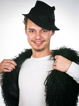 exaltation: trendy young man closed into the fur vest Stock Photo